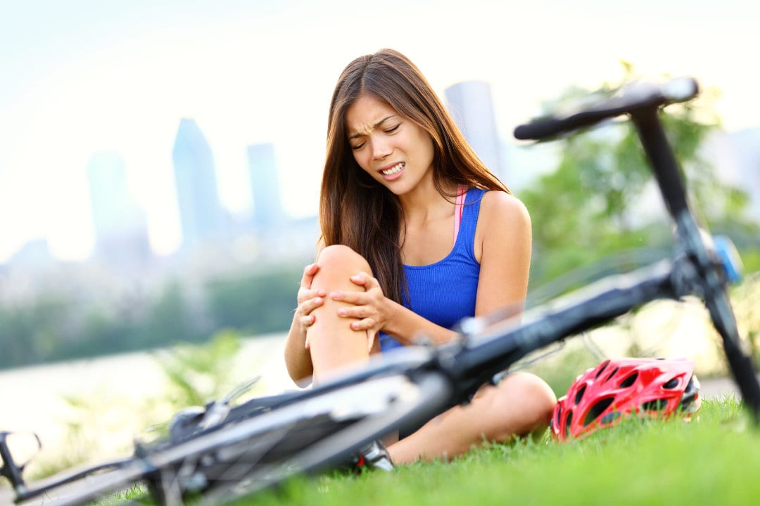 Knee pain bike injury woman suffering from one of the most common sports injuries