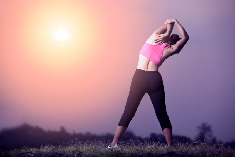 Woman stretching muscle before or after exercise, passive stretching triceps muscle for warm up or cool down, sunset land scape and Asian female with exercise posture, health care and healthy concept