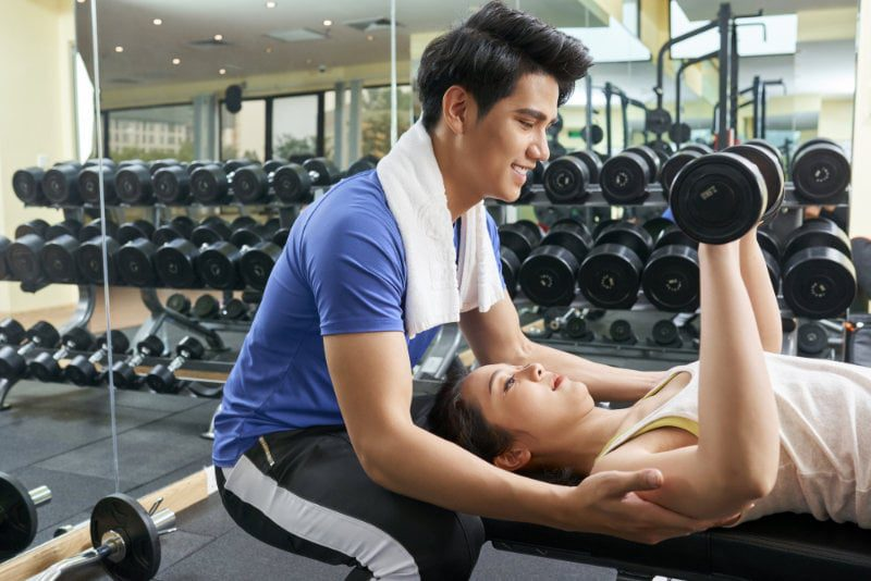Woman lifting dumbbells with instructor