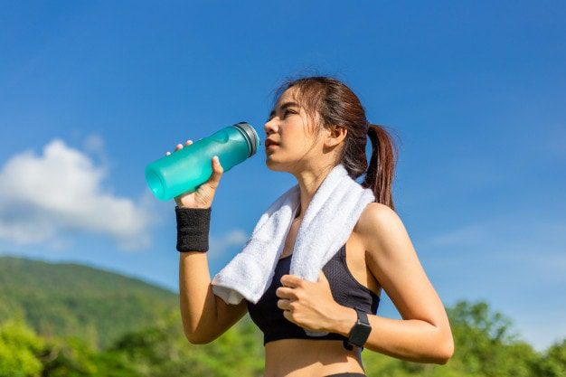 beautiful young asian woman exercising morning running track taking rest drink water